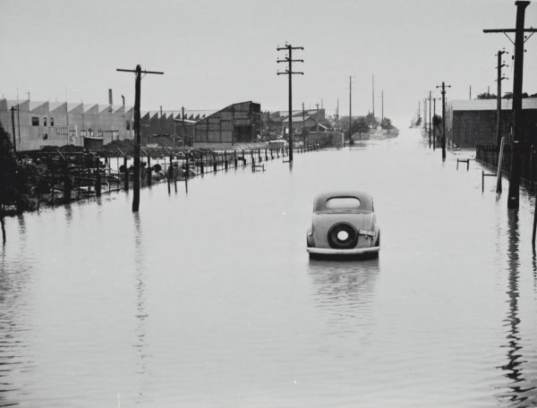 Car abandoned in the middle of a flooded thoroughfare.