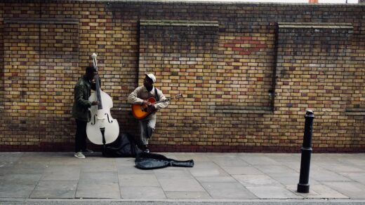 Two musicians performing on the sidewalk, by Tim Bechervaise. From Unsplash.