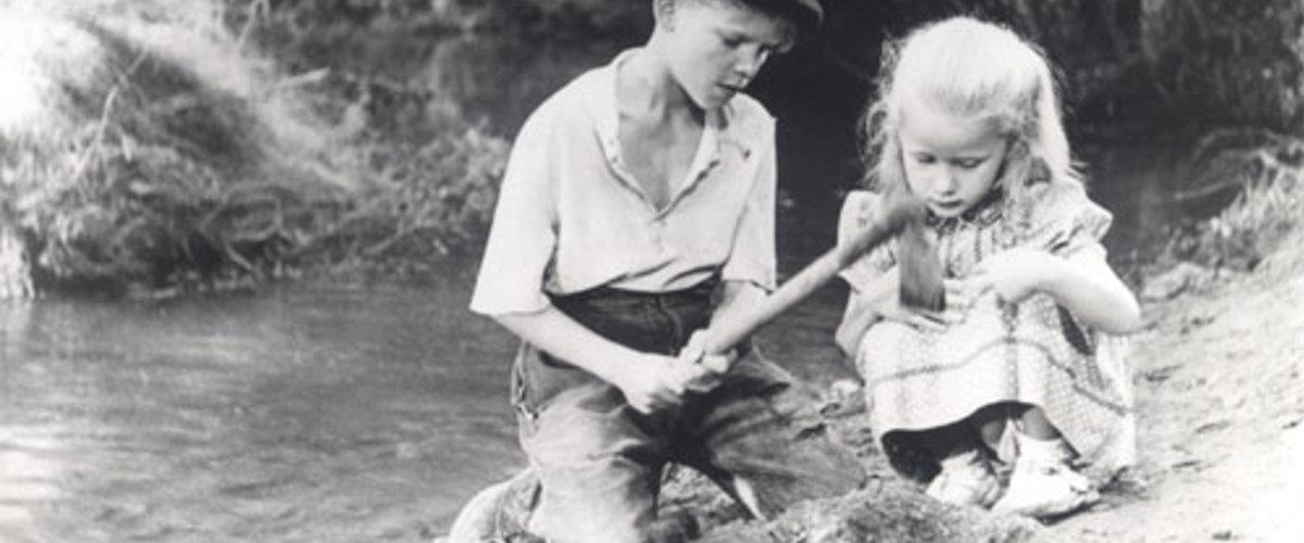 Michel helps Brigitte dig a grave for her dead puppy in the 1952 film Forbidden Games